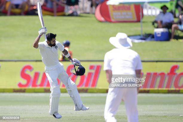 India's captain Virat Kohli raises his bat and helmet as he celebrates scoring a century during the third day of the second Test cricket match...