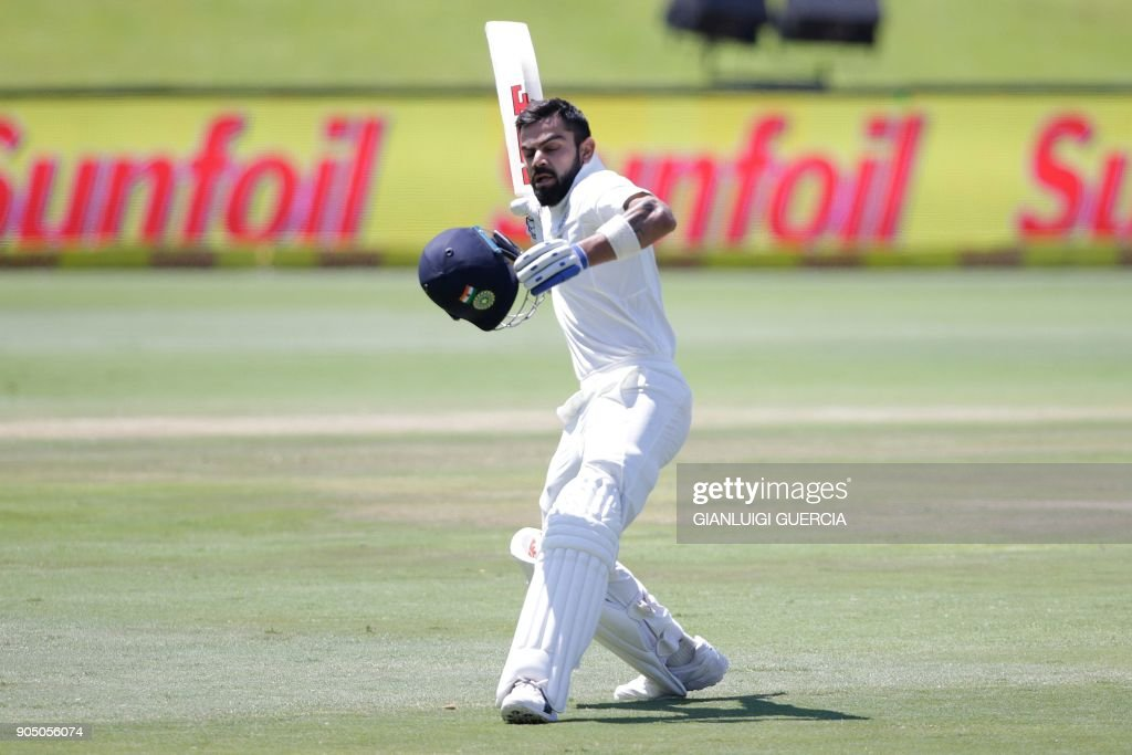 India's captain Virat Kohli raises his bat and helmet as he celebrates scoring a century (100 runs) during the third day of the second Test cricket match between South Africa and India at Supersport cricket ground on January 15, 2018 in Centurion, South Africa. /