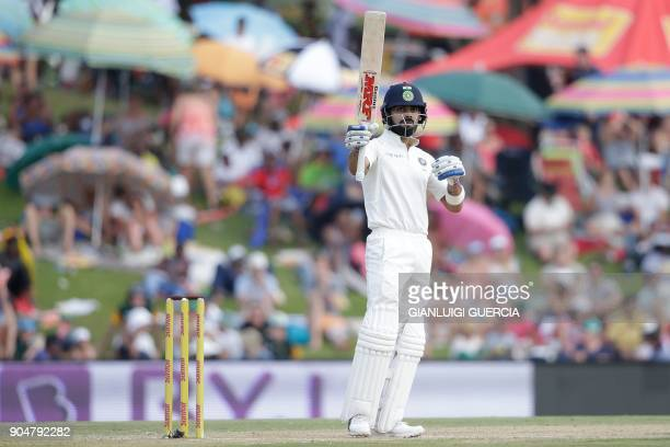 India's captain Virat Kohli raises his bat as he celebrates scoring half century during the second day of the second Test cricket match between South...