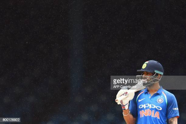 TOPSHOT India's captain Virat Kohli waits to play as it rain during the first One Day International match between West Indies and India at the...
