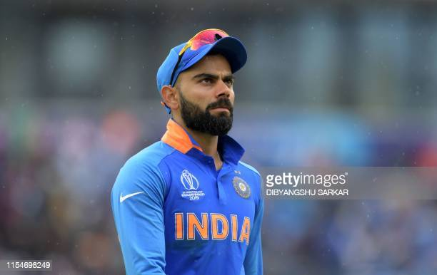 India's captain Virat Kohli walks off the field as rain falls during the 2019 Cricket World Cup first semi-final between India and New Zealand at Old...