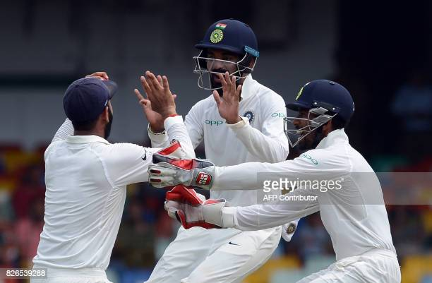 India's Cheteshwar Pujara celebrates with his teammates after taking a catch to dismiss Sri Lanka's Angelo Mathews during the third day of the second...