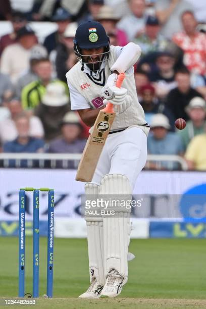 India's Cheteshwar Pujara defends as he faces his first delivery on the second day of the first cricket Test match of the India Tour of England 2021...