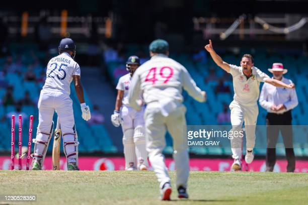 India's Cheteshwar Pujara is clean bowled off Australia's Josh Hazlewood during the fifth day of the third cricket Test match between Australia and...