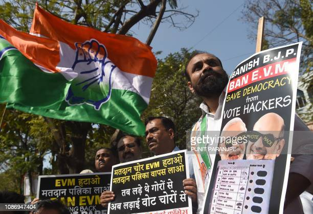 India's Congress Party activists hold placards as they take part in a demonstration to protest against the use of Electronic Voting Machines during...