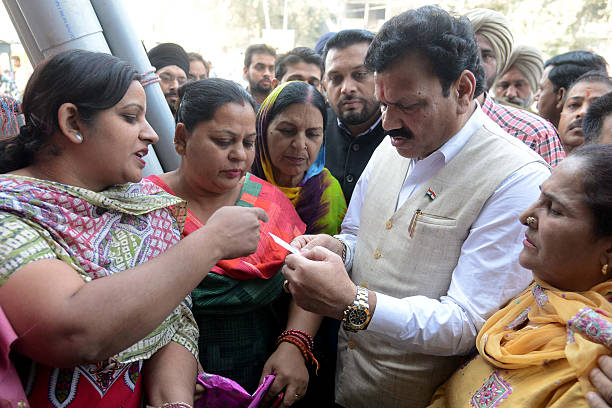 India`s Congress Party official and National Commission for Scheduled Castes vicechairman Raj Kumar Verka listens to people`s problems as they wait...