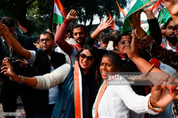 India's Congress party supporters celebrate outside the party headquarters in New Delhi on December 11 as vote counting in five Indian states began...