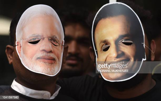 India's Congress party workers wear masks of Indian Prime Minister Narendra Modi and business tycoon Anil Ambani as they pose during a protest...