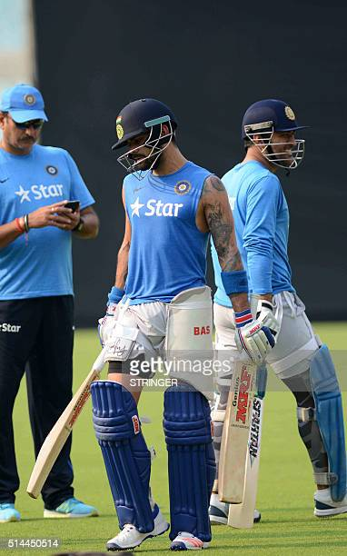India's cricket captain Mahendra Singh Dhoniand teammate Virat Kohliwalk past India's Team Director Ravi Shastrias they take part in a practice...