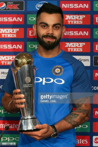 India's cricket captain Virat Kohli poses with the ICC Champions Trophy 2017 trophy at a press conference in The Grange in London on May 25 ahead of...