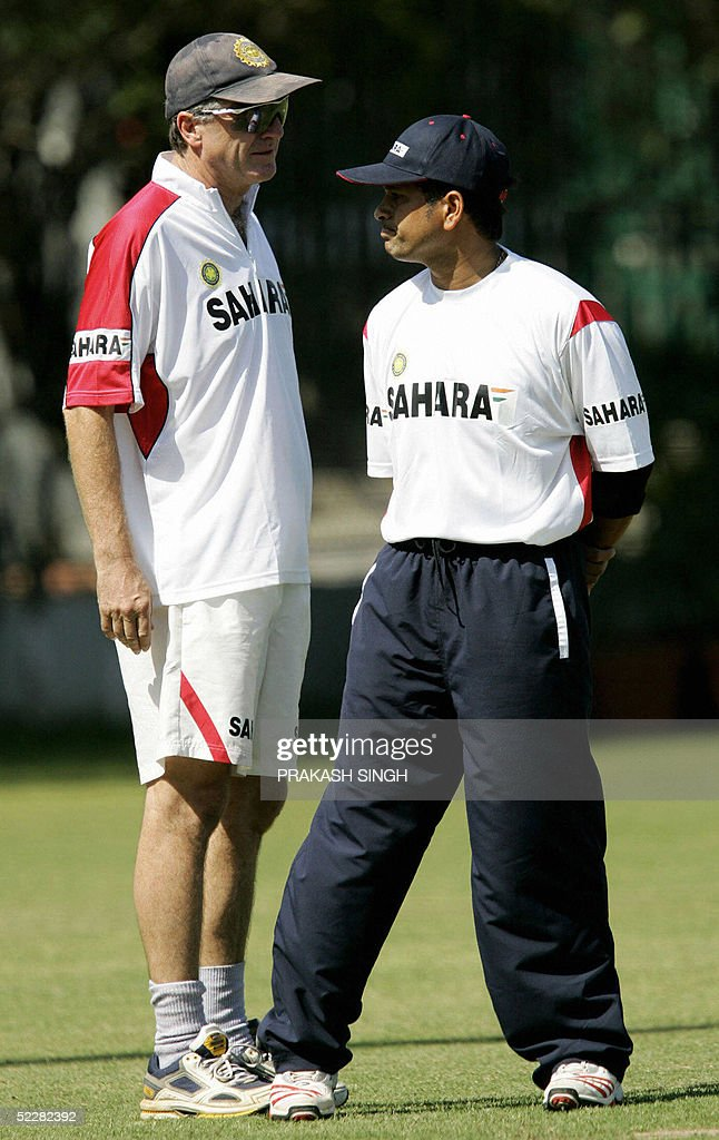 India`s cricket coach John Wright talks to Indian cricketer Sachin Tendulkar during a practice session at the stadium in Mohali near Chandigarh 06...