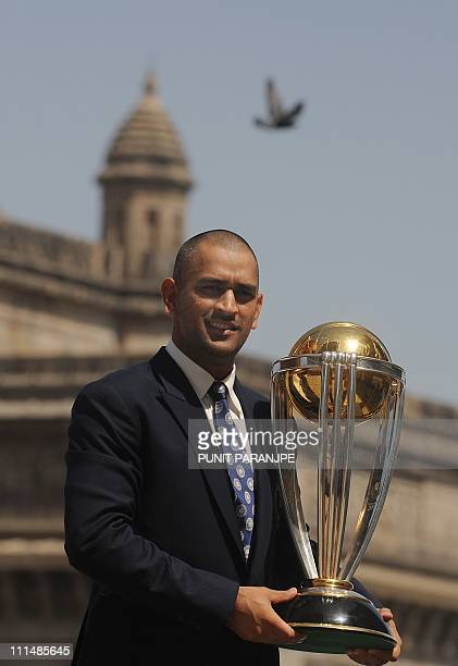 India's cricket team captain Mahendra Singh Dhoni poses with the ICC Cricket World Cup trophy with The Gateway of India monument in the background...
