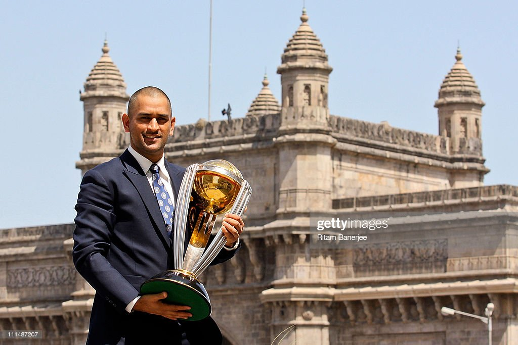India's cricket team captain Mahendra Singh Dhoni poses with the ICC Cricket World Cup Trophy, with the Gateway of India in the backdrop, during a photo call at the Taj Palace Hotel on April 3, 2011 in Mumbai, India.