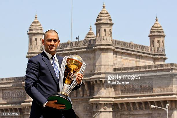 India's cricket team captain Mahendra Singh Dhoni poses with the ICC Cricket World Cup Trophy, with the Gateway of India in the backdrop, during a...