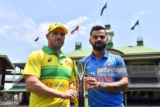 India's cricket team captain Virat Kohli and his Australian counterpart Aaron Finch pose with the One Day International series trophy at the Sydney...