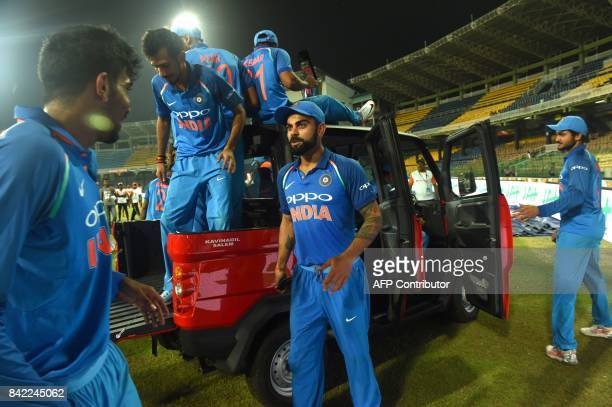 India's cricket team including captain Virat Kohli celebrate on a truck while driving it around the ground after winning the match and the series...