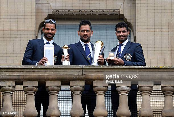 India's cricketers Shikhar Dhawan Mahendra Sing Dhoni and Ravindra Jadeja pose for pictures with the ICC Champions Trophy in Birmingham central...