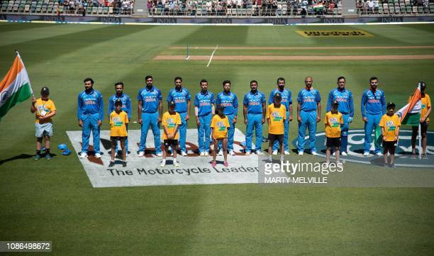 India's cricketers stand for the national anthems at the start of the first oneday international cricket match between New Zealand and India at...