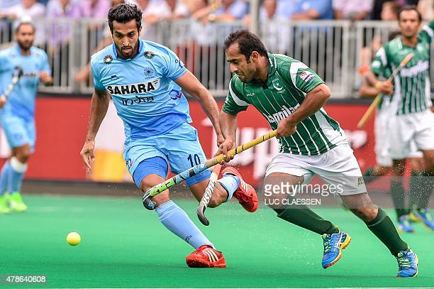 India's Dharamvir Singh vies with Pakistan's Mahmood Rashid during the field hockey match between Pakistan and India in the men's Group A of the...