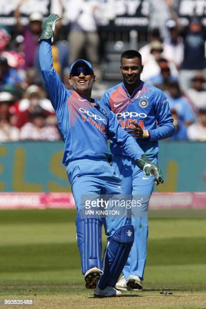 India's MS Dhoni celebrates taking the catch to dismiss England's Eoin Morgan for six runs during the third international Twenty20 cricket match...