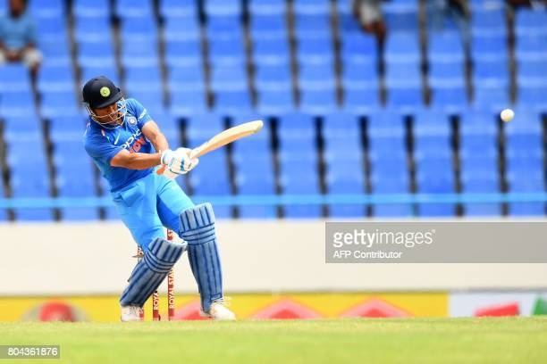 India's MS Dhoni hits a boundary during the third One Day International match between West Indies and India at the Sir Vivian Richards Cricket Ground...