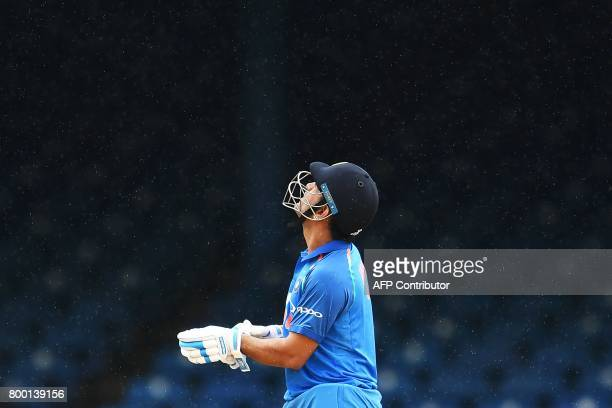 India's MS Dhoni looks up as it rain during the first One Day International match between West Indies and India at the Queen's Park Oval in Port of...
