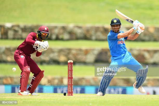 India's MS Dhoni plays a shot as West Indies' wicketkeeper Shai Hope looks on during the third One Day International match between West Indies and...