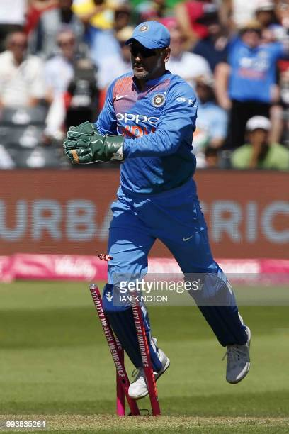 India's MS Dhoni takes the catch to dismiss England's Eoin Morgan for six runs and then runs into the wicket during the third international Twenty20...
