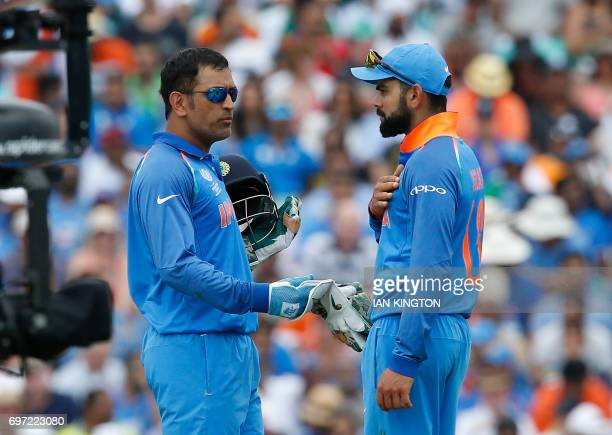 India's MS Dhoni talks to India's captain Virat Kohli during the ICC Champions Trophy final cricket match between India and Pakistan at The Oval in...