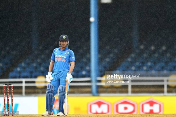 India's MS Dhoni waits for umpires decision as rain interrupt the first One Day International match between West Indies and India at the Queen's Park...
