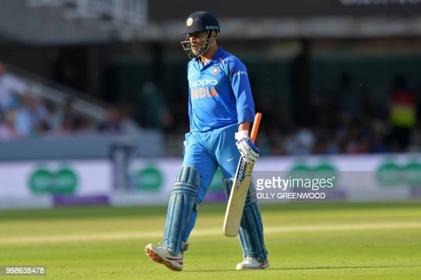 India's MS Dhoni walks back to the pavilion after losing his wicket for 37 during the second One Day International cricket match between England and...