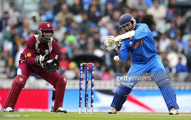 India's Dinesh Karthik plays a shot as West Indies wicketkeeper Johnson Charles looks on during the 2013 ICC Champions Trophy cricket match between...