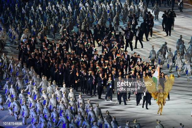India's flagbearer Neeraj Chopra leads the delegation during the opening ceremony of the 2018 Asian Games at the Gelora Bung Karno main stadium in...