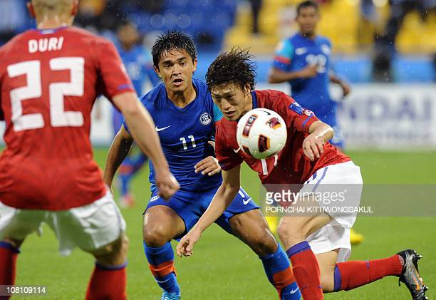 India's forward Sunil Chhetri eyes the ball as he vies with South Korea's midfielder Lee ChungYong during their 2011 Asian Cup group C football match...