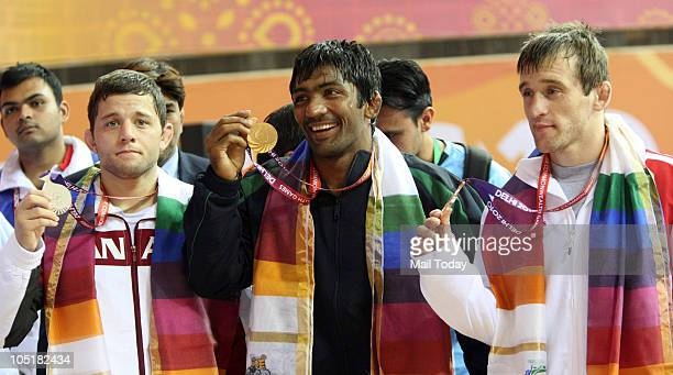 India's gold medalist Yogeshwar Dutt , Canada's silver medalist James Mancini and England's bronze medalist Sasha Madyarchyk pose at the Indira...