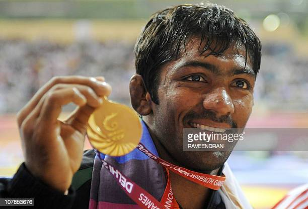 India's gold medalist Yogeshwar Dutt poses at the awards ceremony for 60kg men's freestye wrestling at the Commonwealth Games 2010 in New Delhi on...