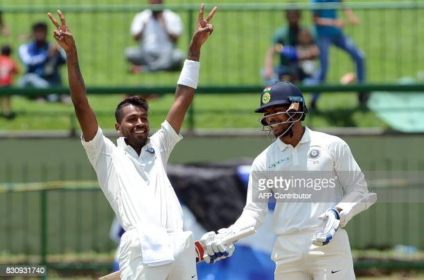 India's Hardik Pandya celebrates after scoring a century as his teammate Umesh Yadav looks on during the second day of the third and final Test match...