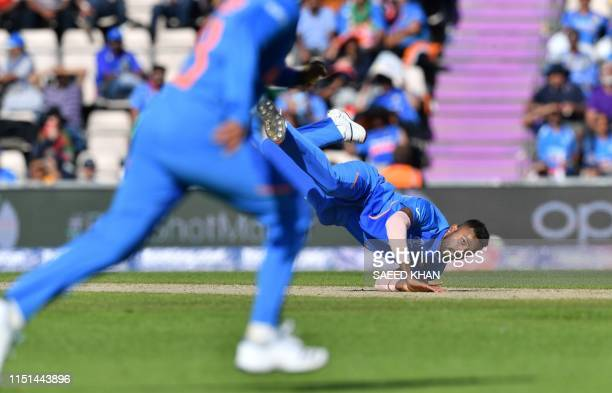 India's Hardik Pandya dives to field a ball off his own bowling during the 2019 Cricket World Cup group stage match between India and Afghanistan at...