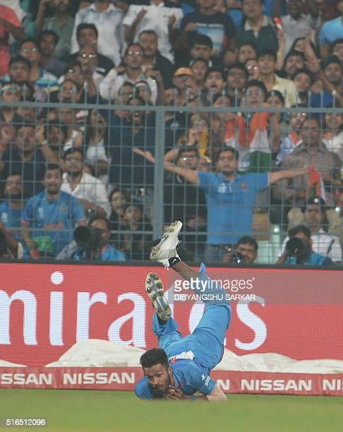 India's Hardik Pandya dives to take a catch off Pakistan's Sharjeel Khan during the World T20 cricket tournament match between India and Pakistan at...