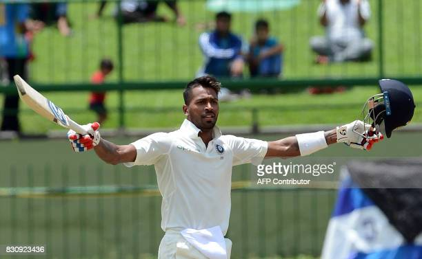 India's Hardik Pandya raises his bat and helmet in celebration after scoring a century during the second day of the third and final Test match...