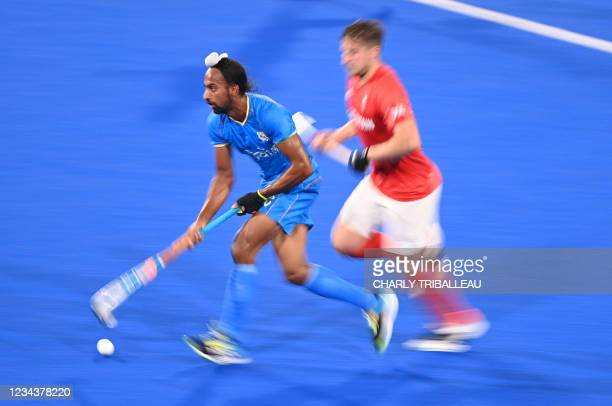 India's Hardik Singh carries the ball during the men's quarter-final match of the Tokyo 2020 Olympic Games field hockey competition against Britain,...