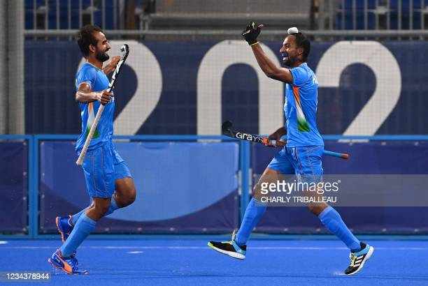 India's Hardik Singh celebrates with a teammate after scoring against Britain during their men's quarter-final match of the Tokyo 2020 Olympic Games...