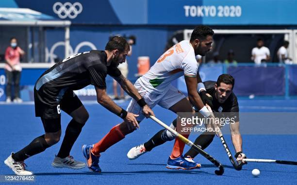 India's Harmanpreet Singh is tackled by Argentina's Nahuel Salis and Agustin Alejandro Mazzilli during their men's pool A match of the Tokyo 2020...