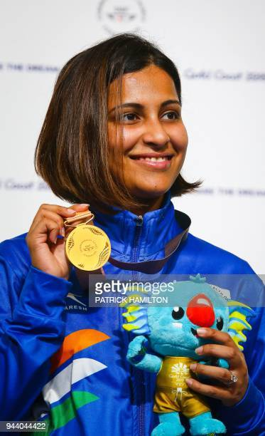 India's Heena Sidhu poses with the gold medal from the podium at the awards ceremony following her victory in the women's 25m pistol shooting during...