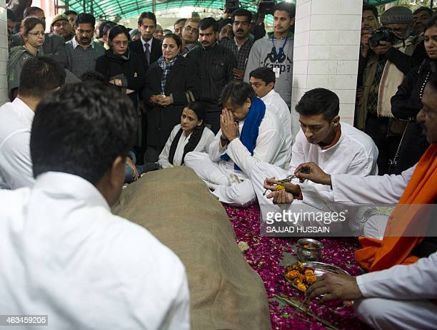 India's Human Resources Minister Shashi Tharoor gestures as he sits with other relatives and friends alongside the body of his wife Sunanda Pushkar...