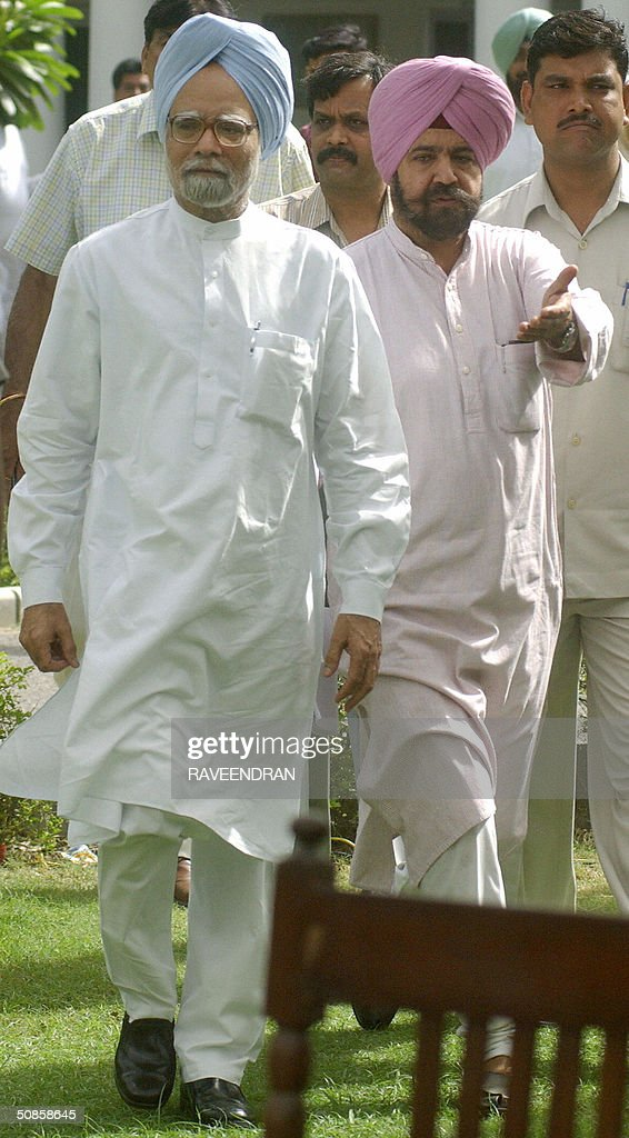 India's incoming prime minister Manmohan Singh(L) is guided by an unidentified supporter as he walks towards the site of a press conference at his residence in New Delhi,20 May 2004. Singh pledged to push forward dialogue with neighbouring Pakistan, saying friction between the rivals should be 'a thing of the past.' and 'We seek the most friendly relations with our neighbours, more so with Pakistan than with any other,'.