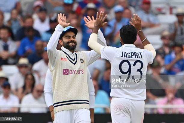 India's Jasprit Bumrah celebrates with India's captain Virat Kohli after trapping England's Stuart Broad LBW during play on the first day of the...