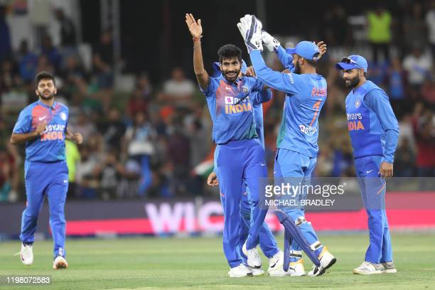 Indias Jasprit Bumrah celebrates with teammates after taking the wicket of New Zealands Daryl Mitchell during the fifth Twenty20 cricket match...