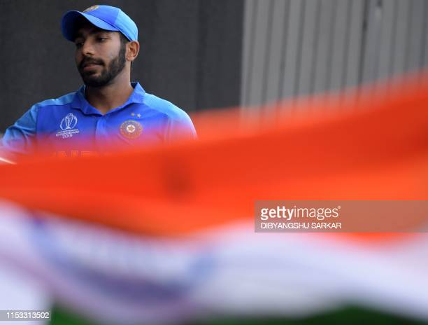 India's Jasprit Bumrah walks to the pavilion in front of the Indian national flag after victory in the 2019 Cricket World Cup group stage match...