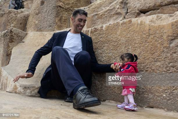 India's Jyoti Amge the world's shortest woman poses for a picture with Sultan Kosen of Turkey the world's tallest man at the foot of one of the three...